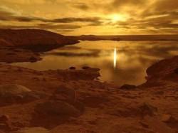 Los vientos estacionales podrían por fin estar levantando olas en los lagos de Titán. Ilustración por Ron Miller