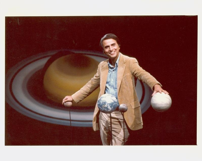 Carl Sagan sosteniendo con las manos los globos de los planetas. Crédito: Eduardo Castaneda