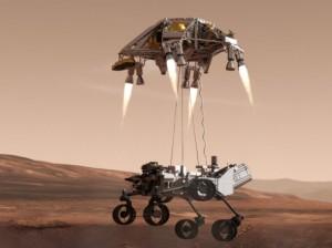 """Imagen del rover Curiosity aterrizando en Marte, usando un """"sky crane""""."""